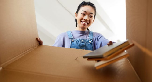 Low angle view at young Asian woman looking into cardboard box and smiling happily while packing or unpacking for new home, copy space