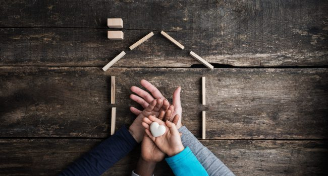 Top view of a family of four placing hands one on top of the other in a conceptual image of love, togetherness and safety.