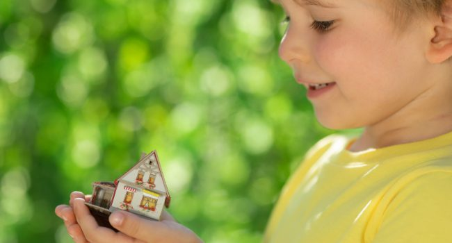 Child holding eco house in hands against spring green background. Real estate and Earth day holiday concept